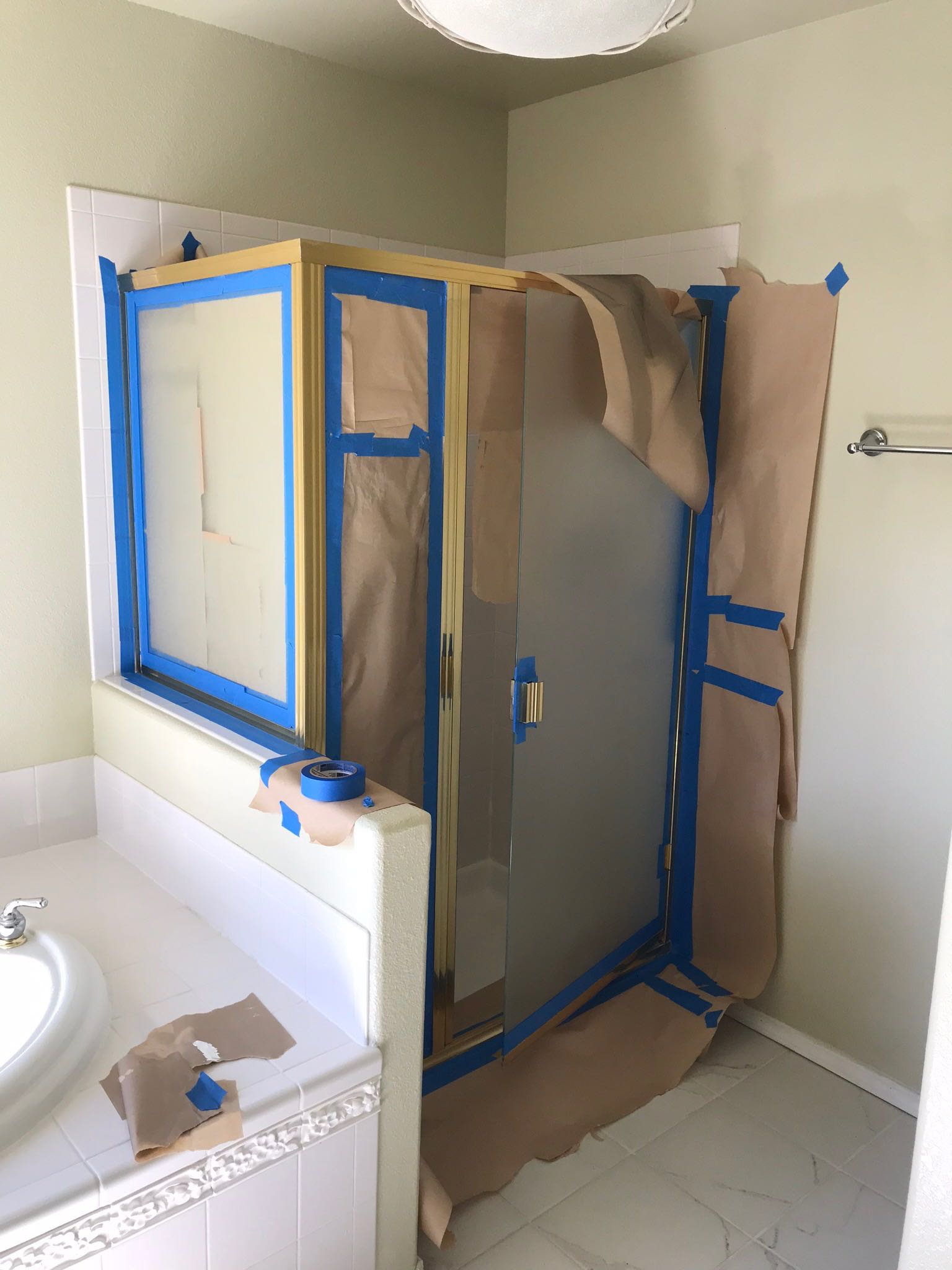 Tape the shower door before spray painting it to cover the brass